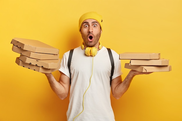 Colpo isolato di uomo di consegna sorpreso tiene diverse scatole di cartone con pizza italiana in entrambe le mani, scioccato per portare fast food in un posto non corretto, indossa una maglietta bianca, cuffie intorno al collo