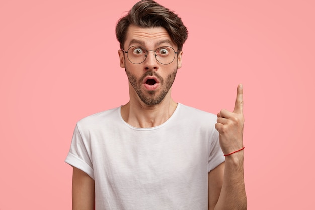 Isolated shot of surprised unshaven man gasps from amazement, points with fore finger upwards, wears round glasses and white t shirt, models against pink  wall, demonstrates something above