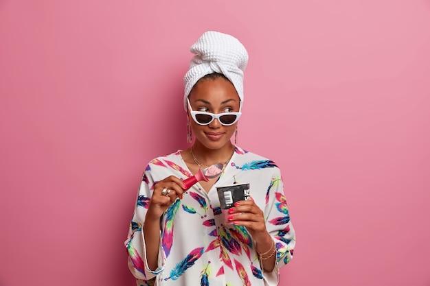 Colpo isolato di premurosa donna dalla pelle scura compiaciuta mangia dessert congelato trascorre il tempo libero a casa vestita in vestaglia avvolto asciugamano da bagno sulla testa dopo aver fatto la doccia isolata sulla parete rosa