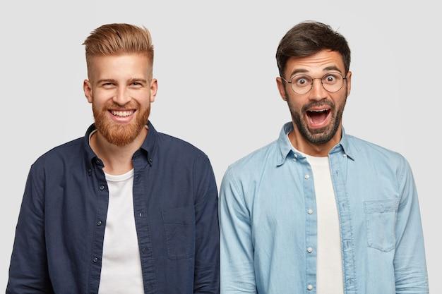 Colpo isolato di due ragazzi barbuti sorpresi gioiosi esprimono emozioni positive