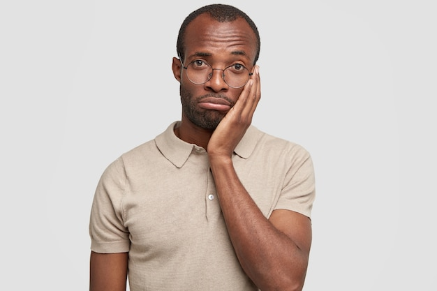 Colpo isolato di infelice afroamericano maschio borse labbra e guarda disperatamente a porte chiuse
