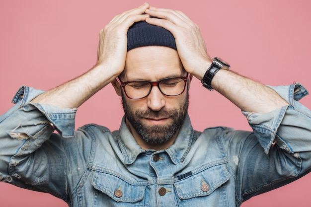 Isolated shot of unhappy desperate man with stubble keeps hands on head, wears fashionable clothing