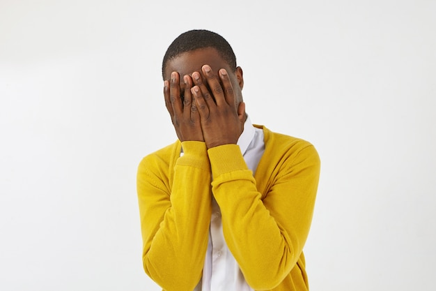 Isolated shot of unrecognizable dark skinned male dressed in yellow cardigan posing , covering face with both hands, hiding himself, feeling guilty, ashamed, embarrassed, shy or scared