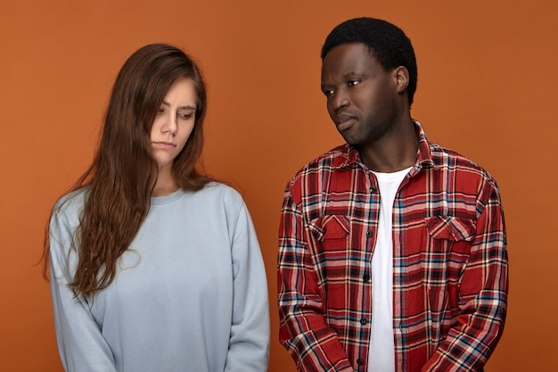 Isolated shot of upset young caucasian female and afro american male having unhappy facial expressions because they have to break up. interracial depressed couple facing problems, being sad