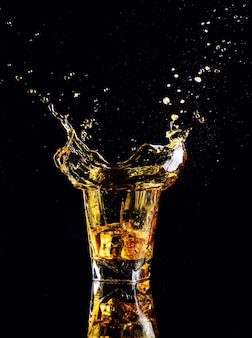 Isolated shot of whiskey with splash on black, brandy in a glass