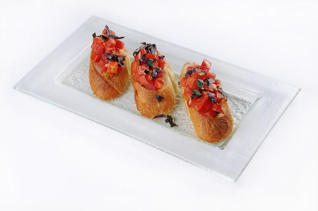 Colpo isolato di un piatto bianco con tre bruschette classiche
