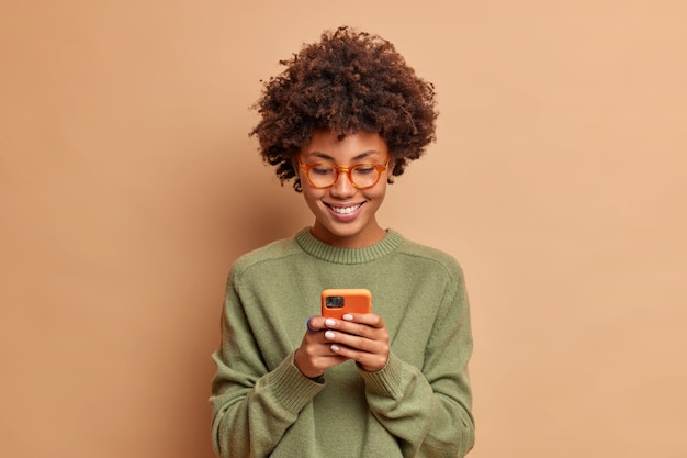 Isolated shot of woman uses smartphone application enjoys browsing social media creats news content makes online order wears spectacles and casual jumper poses over beige studio wall