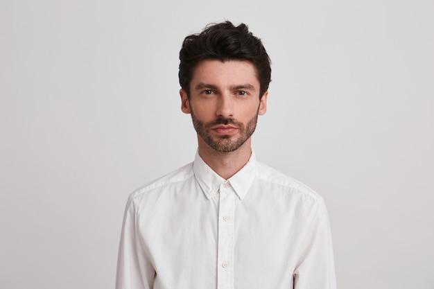 Colpo isolato di giovane uomo bello con la barba, indossa una camicia bianca casual, ha un'espressione seria, in piedi su bianco