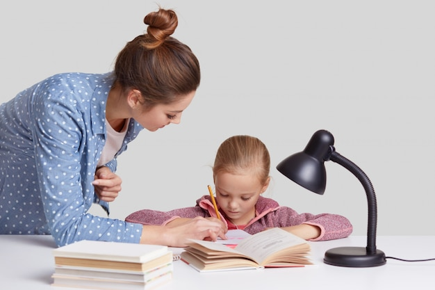 Isolated shot of young mum in fashionable shirt helps to write her small daughter, read books, do homework together, use reading lamp, isolated over white wall. children and learning concept