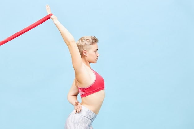 Isolated side view image of stylish sporty girl with blonde hair training  using resistance band to improve shoulder flexibility and open chest, backbending. sports and fitness concept