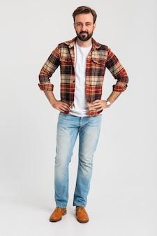 Uomo barbuto bello sorridente isolato in abito hipster vestito di jeans
