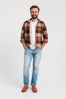 Изолированные улыбается красивый бородатый мужчина в хипстерской одежде, одетый в джинсы