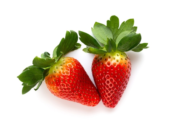 Isolated strawberries. two whole strawberry fruits and half isolated on white surface.