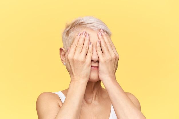 Immagine di studio isolato di nonna irriconoscibile con i capelli biondi corti che gioca a nascondino con i suoi nipoti, coprendo gli occhi con entrambe le mani.