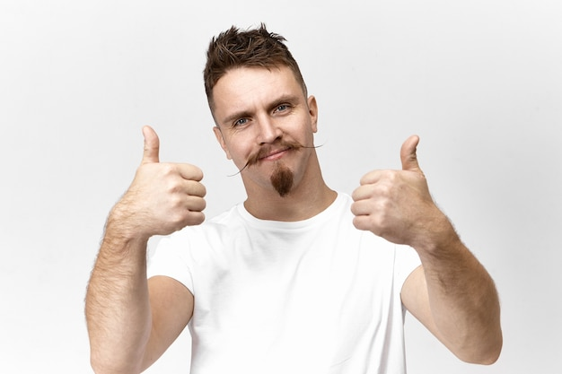 Isolated studio shot of handsome trendy young caucasian man with goatee beard and handlebar mustache looking at camera with positive friendly smile, showing thumbs up sign, liking idea or plan