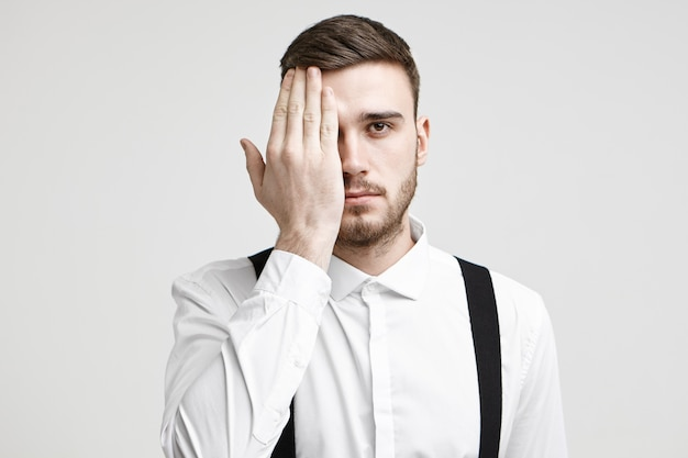 Isolated studio shot of handsome young male corporate worker with bristle and stylish haircut looking at camera, covering one eye with palm as if having his eyes tested during vision examination