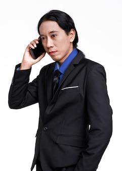 白い背景の上のモバイルスマートフォンでビジネス会話を議論している黒のフォーマルなスーツの立っているアジアのスマートな自信を持って成功した男性実業家起業家の孤立したスタジオショット。