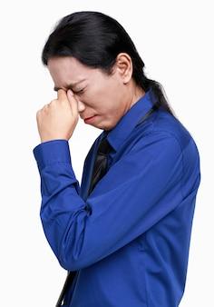 アジアの不幸なストレスの孤立したスタジオショットは、頭に手をつないで立っているビジネスマンの従業員役員のスタッフが白い背景で頭痛の問題を抱えていました。