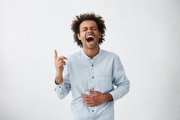 ファンキーな髪の肯定的な陽気な若いアフリカ系アメリカ人男性の分離のスタジオショット