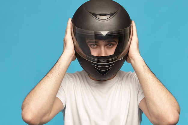 Isolated studio shot of self determined serious young caucasian male biker taking on stylish black motorcycle helmet