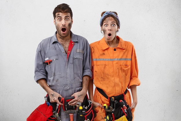 Isolated studio shot of untidy female and male carpenters look with bugged eyes and jaw dropped out