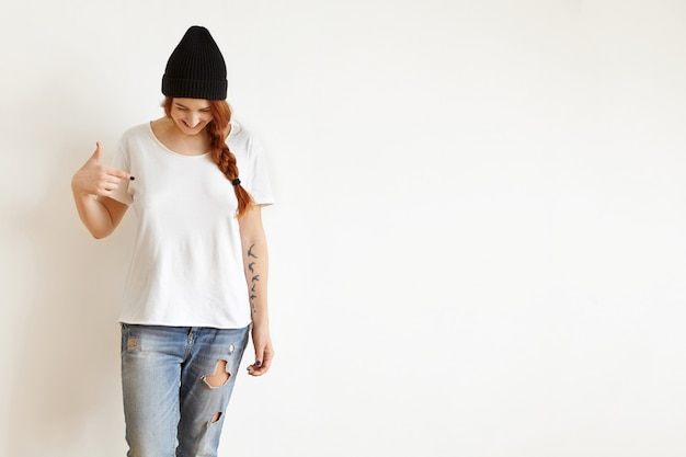 Isolated studio shot of young female with braid looking down as she pointing at her blank white t-shirt