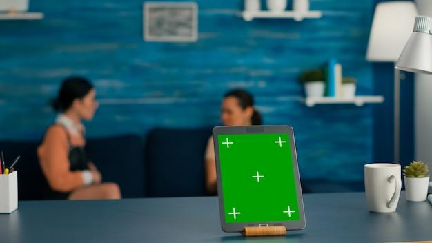 거실의 책상 테이블에 모의 녹색 화면 크로마 키가 서 있는 격리된 태블릿 컴퓨터. 의사 소통에 대해 이야기하는 배경에서 소파에 앉아 두 친구