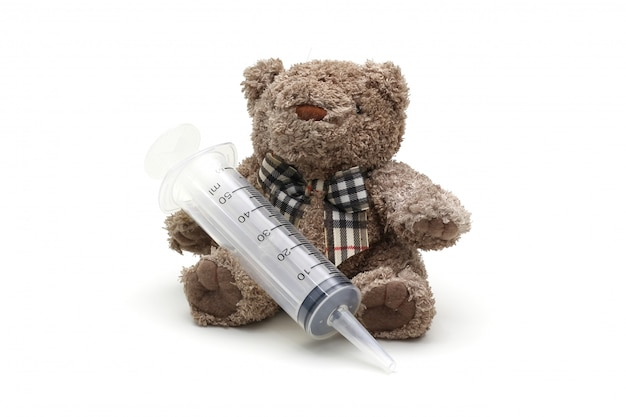 Isolated teddy bear toy holding syringe on white