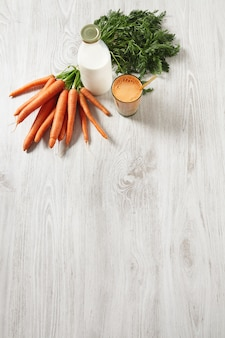 Isolated top view on wooden table, farm carrot harvest lying near bottle and glass filled with mix natural fresh juice and milk with golden drinking straw in it