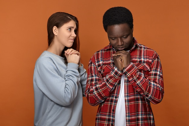 Isolated unhappy depressed young interracial couple white woman and black man facing financial or health problems, praying, holding hands clasped, having mournful facial expressions