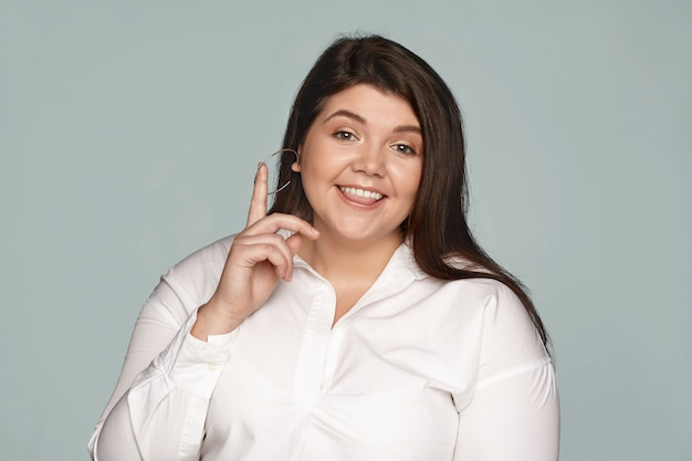 Isolated view of chubby plump young woman manager wearing round earrings and white formal shirt biting tongue and raising finger, having great idea, looking with happy expression
