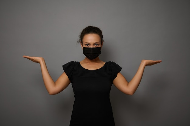 広告のための架空のコピースペースを保持しながら手のひらを上げる黒い保護医療マスクを身に着けている自信を持って穏やかなアフリカの女性の灰色の背景に孤立した腰の長さの肖像画