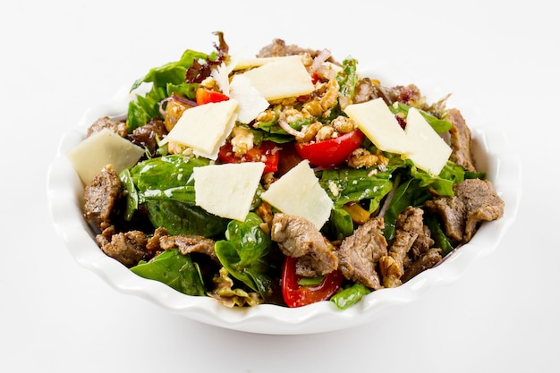 Isolated warm salad with veal and nuts