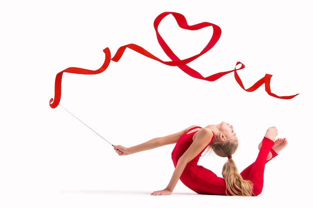 Isolated on white background girl gymnast in a red overalls does exercise with a ribbon, the ribbon is twisted into a heart.