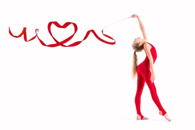 Isolated on white background gymnast in a red suit is exercising with a ribbon, the ribbon is twisted in the heart.