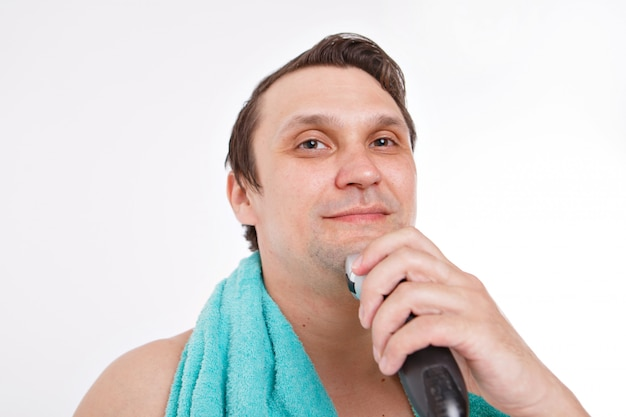 Isolated on a white background: a man shaves his stubble. the guy cleans his beard with an electric razor.