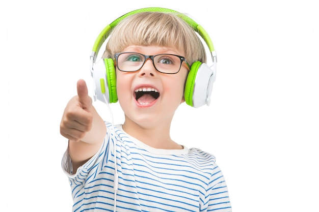Isolated on white cute child listening to the music on earphones. boy on white background with headphones.