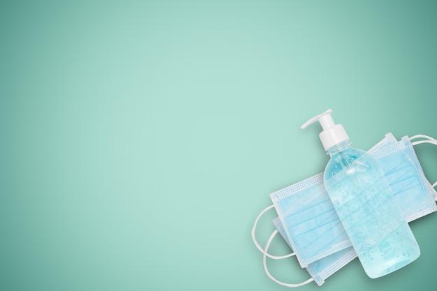 격리 된 흰색 보호 얼굴 마스크 및 알코올 젤 녹색 벽에 코로나 바이러스 또는 covid 19 및 먼지 pm 2.5. 건강 및 위생 장비 개념.