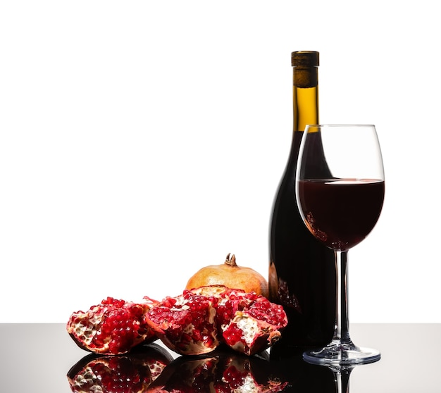Isolated wine bottle, wine glass and juicy pomegranate