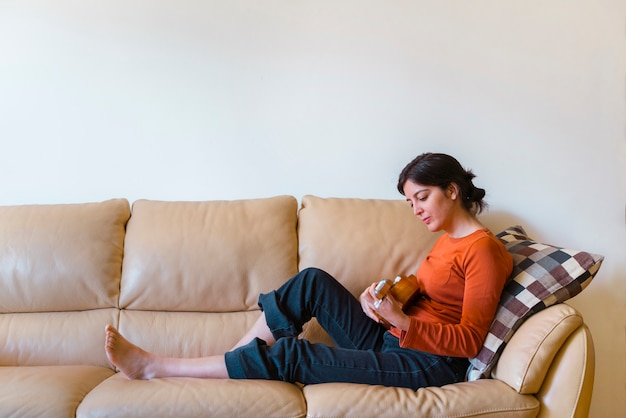 Isolated woman playing small guitar on the couch staying in the house