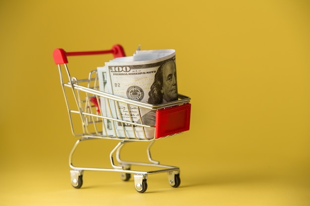 Isolated on yellow shopping cart filled with thai coins.