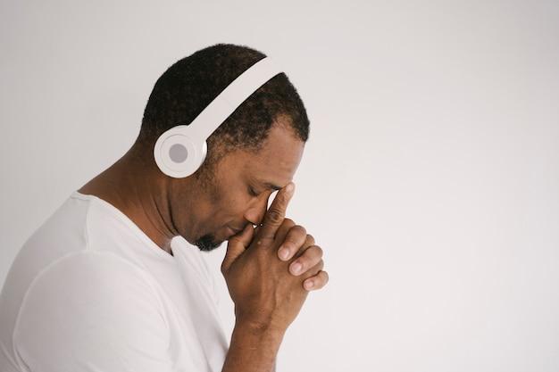 그의 무선 블루투스 화이트 헤드폰에 리듬과 블루스 음악을 듣고 격리 된 젊은 매력적인 남성. 헤드폰 생각에 음악을 듣고 웃는 아프리카 계 미국인 남자의 초상화.