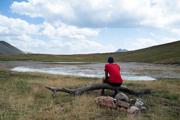 赤いtシャツで山の湖の近くに座っている孤立した若い男トレッキングと瞑想