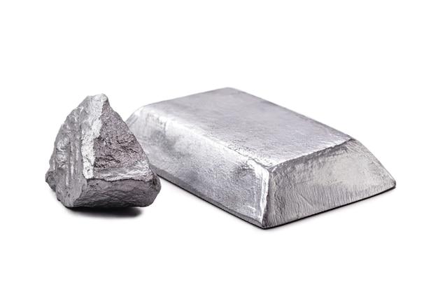 Изолированный слиток цинка или стержень рядом с самородком сырого цинка на изолированном белом фоне, металл, используемый в производстве сплавов и стали.
