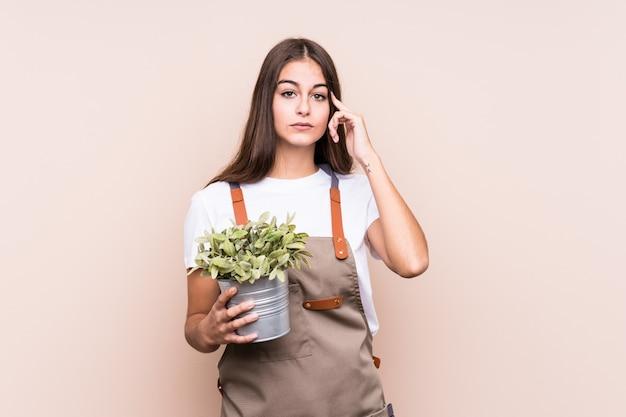 指で植物isolatedpointing寺を保持している若い庭師白人女性、思考、タスクに焦点を当てた。
