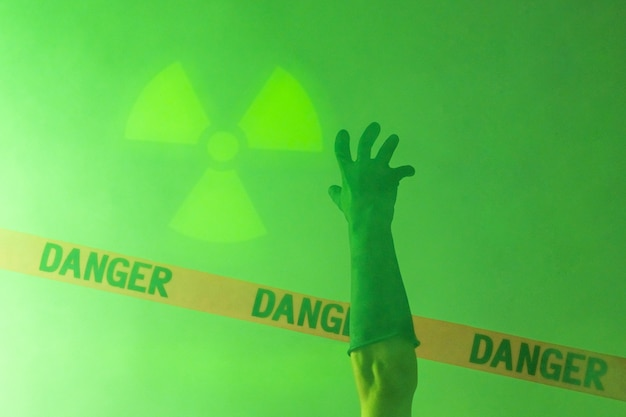 Изоляция. биологическая опасность. человеческая рука в защитных перчатках тянется к красной ленте со словами «опасно». радиоактивный знак.