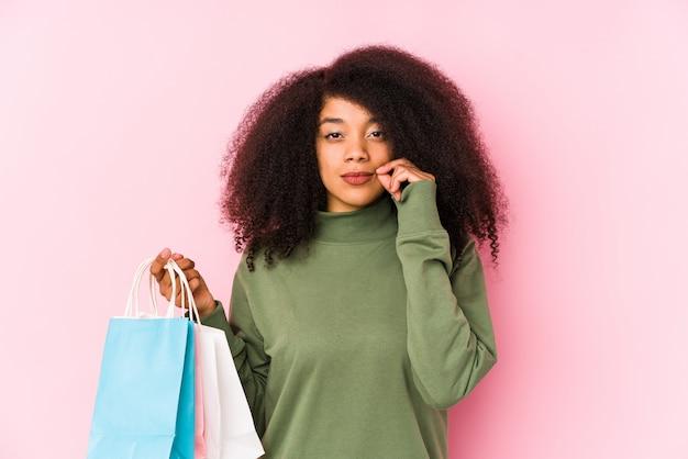 Молодая афро женщина, делающая покупки изолированные молодая афро женщина, делающая покупки isolayoung афро женщина, держащая розы, изолированные пальцами на губах, сохраняя в тайне. <mixto>