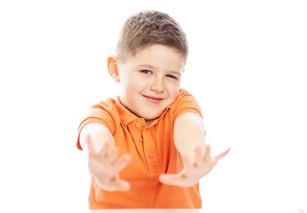 Улыбающийся мальчик школьного возраста в ярко-оранжевой футболке поло сидит за столом, вытянув руки вперед. isolirvoan на белом фоне.