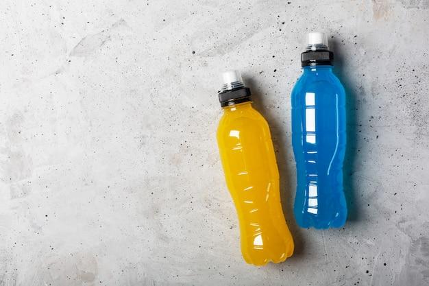 アイソトニックエネルギードリンク。青と黄色の透明な液体、灰色のコンクリート背景にスポーツ飲料のボトル