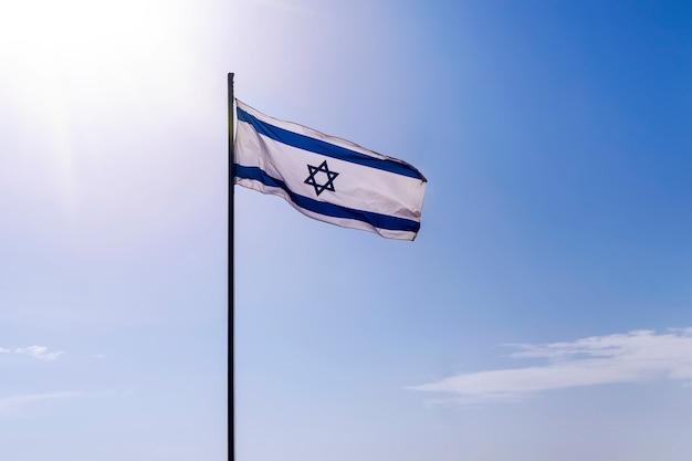 Флаг израиля развевается на ветру в хороший солнечный день на фоне старого города